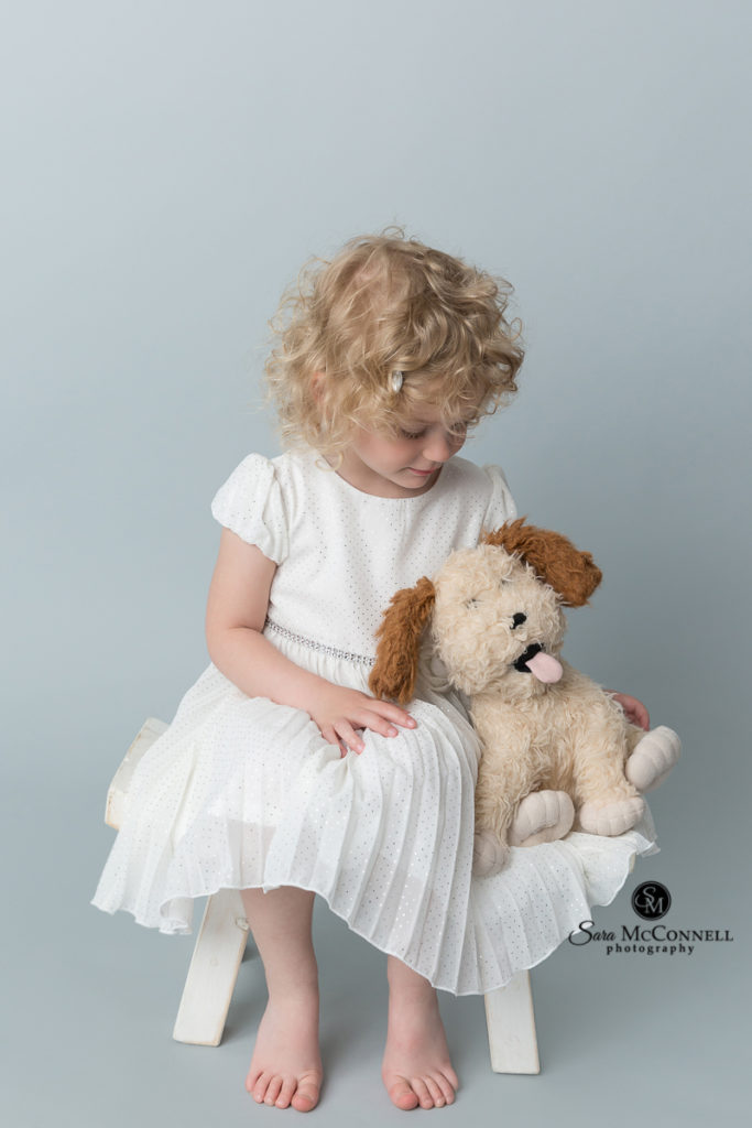 3 year old girl in a white dress holding a stuffed puppy