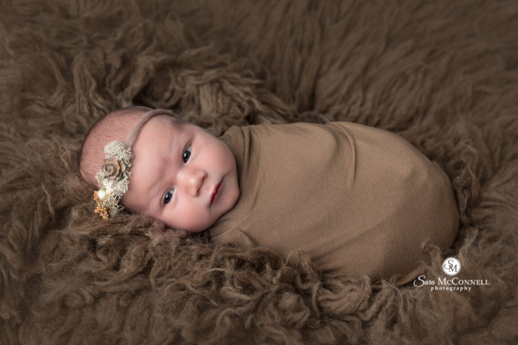 newborn baby wearing a headband lying on a brown fur rug