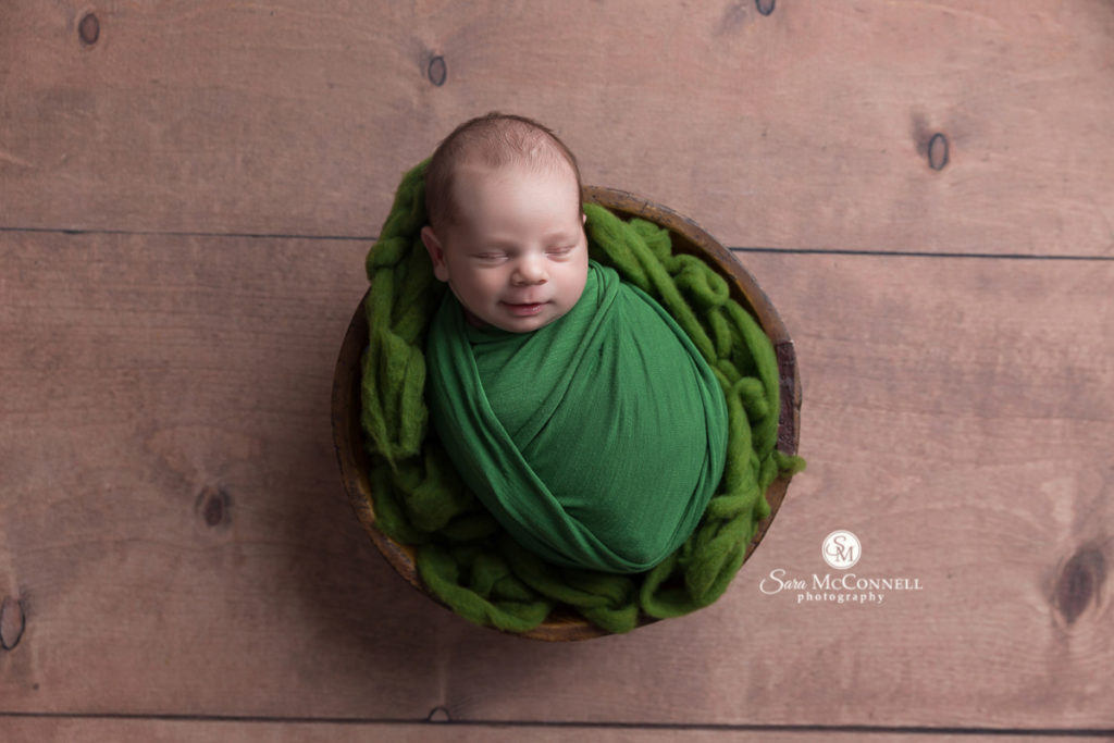 baby wrapped in green sleeping in a wooden basket