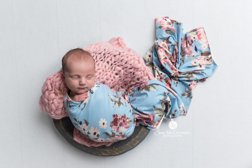 sleeping newborn in a wooden bowl wrapped in floral wrap