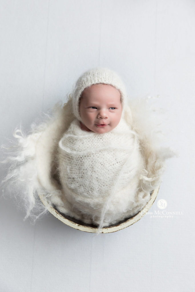 newborn wearing a white hat wrapped in white