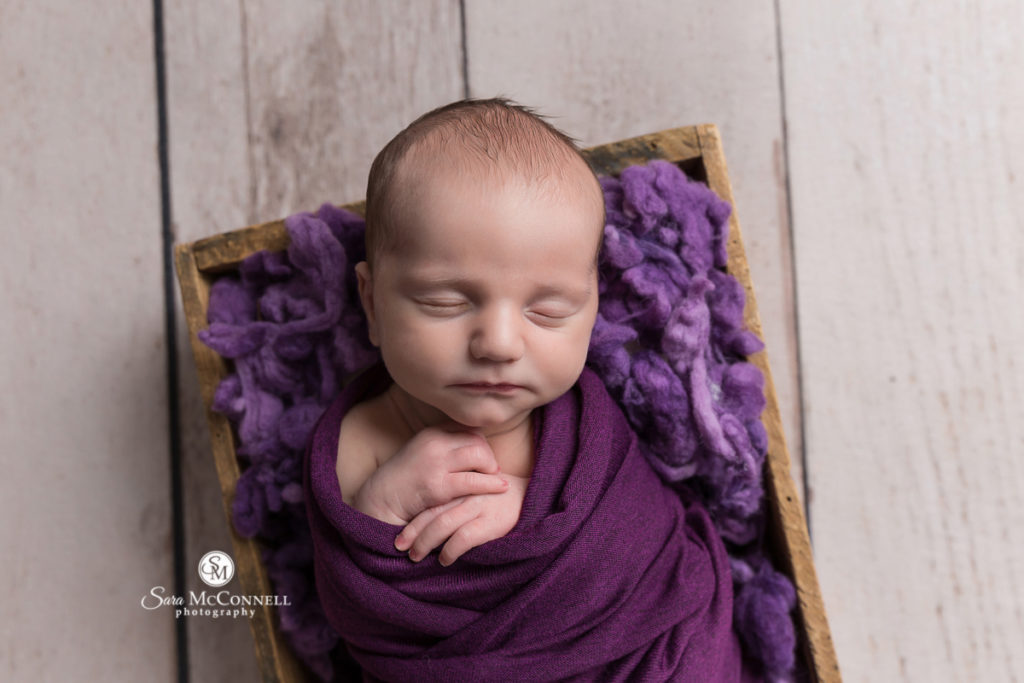 newborn baby wrapped in purple