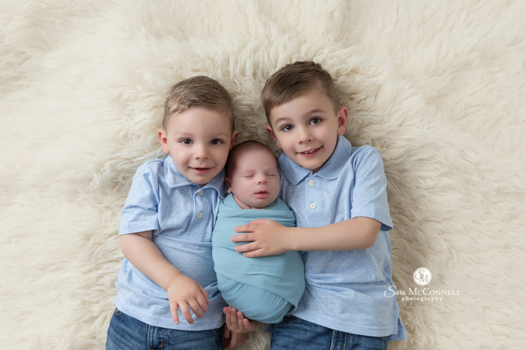 brothers wearing blue tshirts holding baby brother