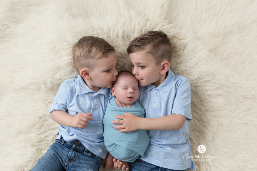 big brothers kissing newborn baby brother's head