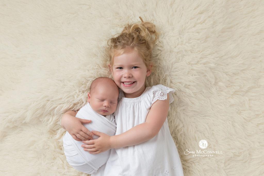 big sister snuggling newborn baby
