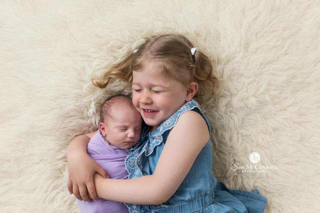 big sister snuggling newborn baby on a fur rug