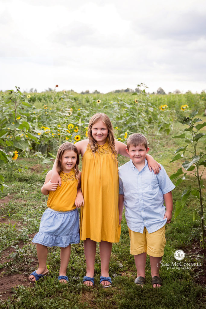 siblings in front of sunflower field