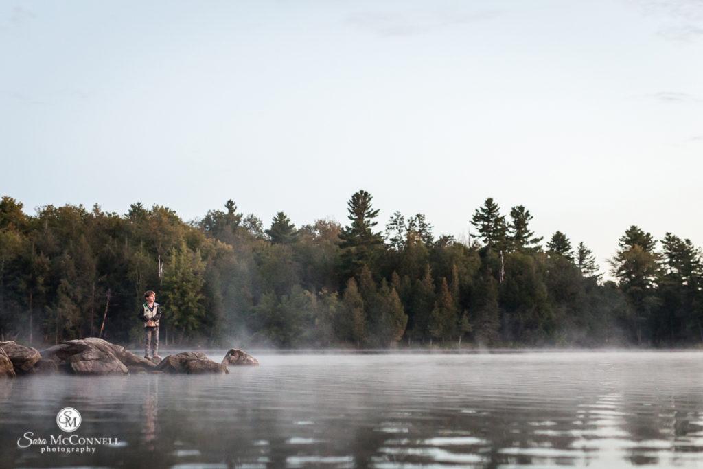 child on rocks near a foggy river