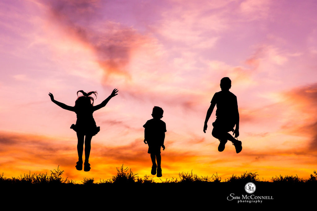 children jumping at sunset