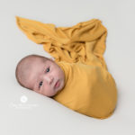 baby wrapped in mustard yellow