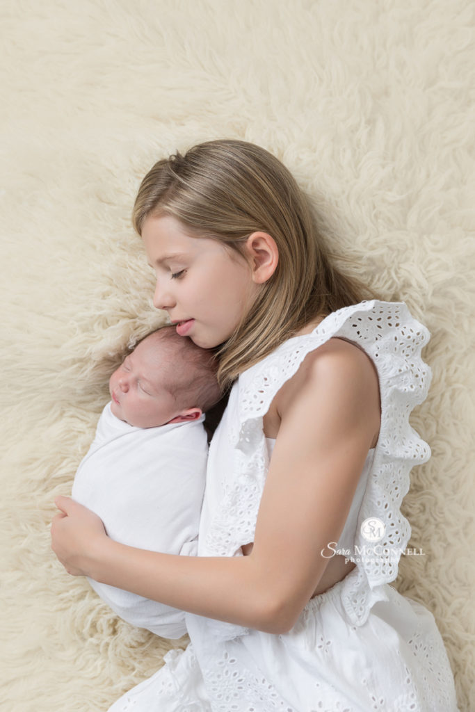 big sister wearing a white dress holding a newborn baby