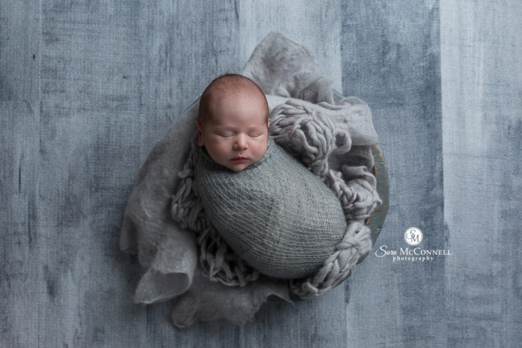 sleeping newborn baby wrapped in grey