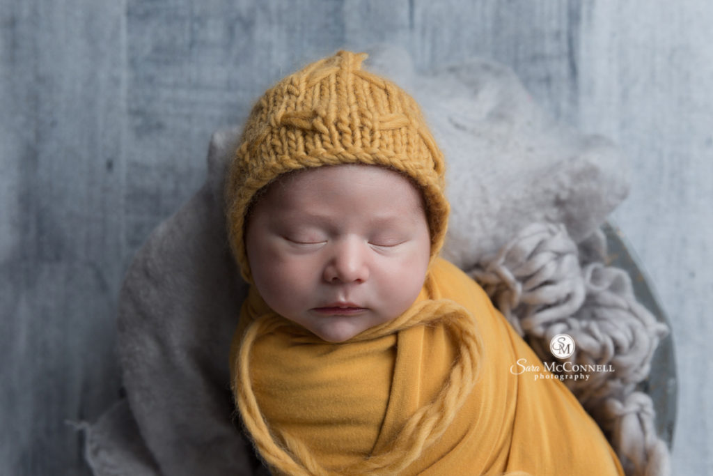 sleeping newborn baby wrapped in yellow