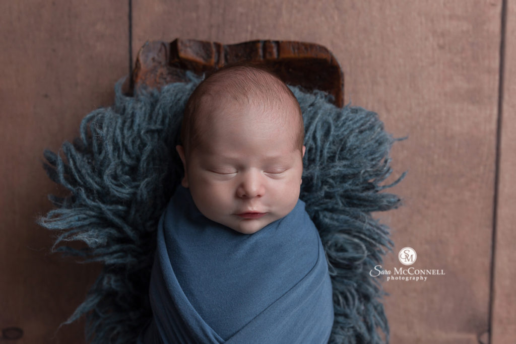 sleeping newborn wrapped in blue