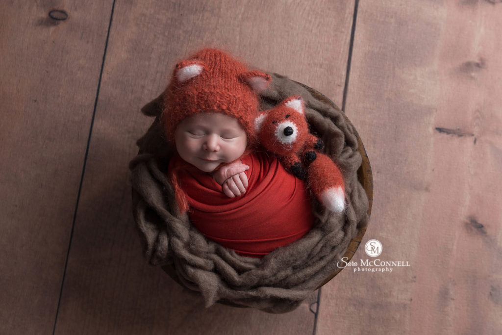 baby wrapped in a blanket wearing a fox hat