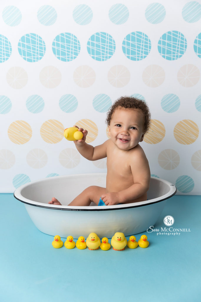 smiling baby playing in the bath tub with rubber duckies