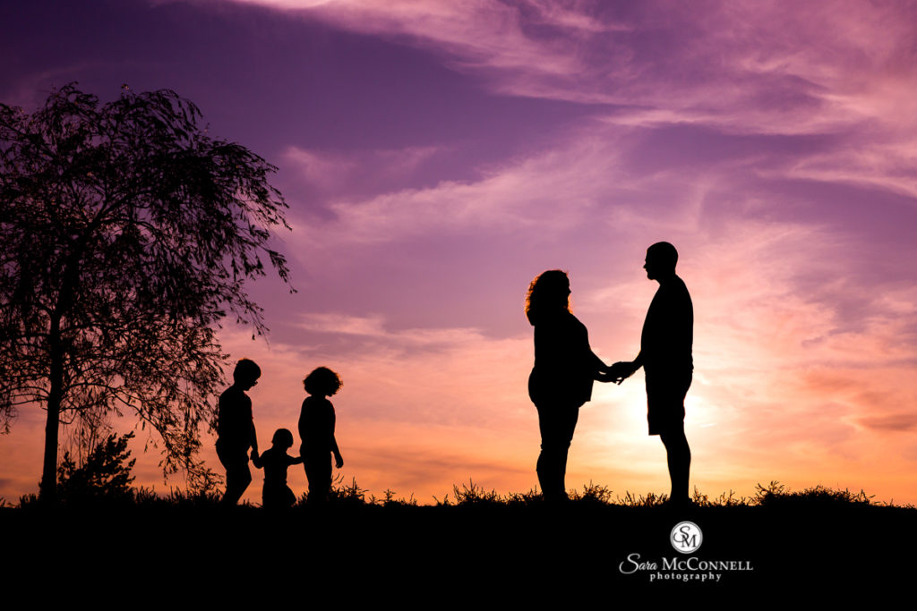 parents holding hands at sunset with children looking on