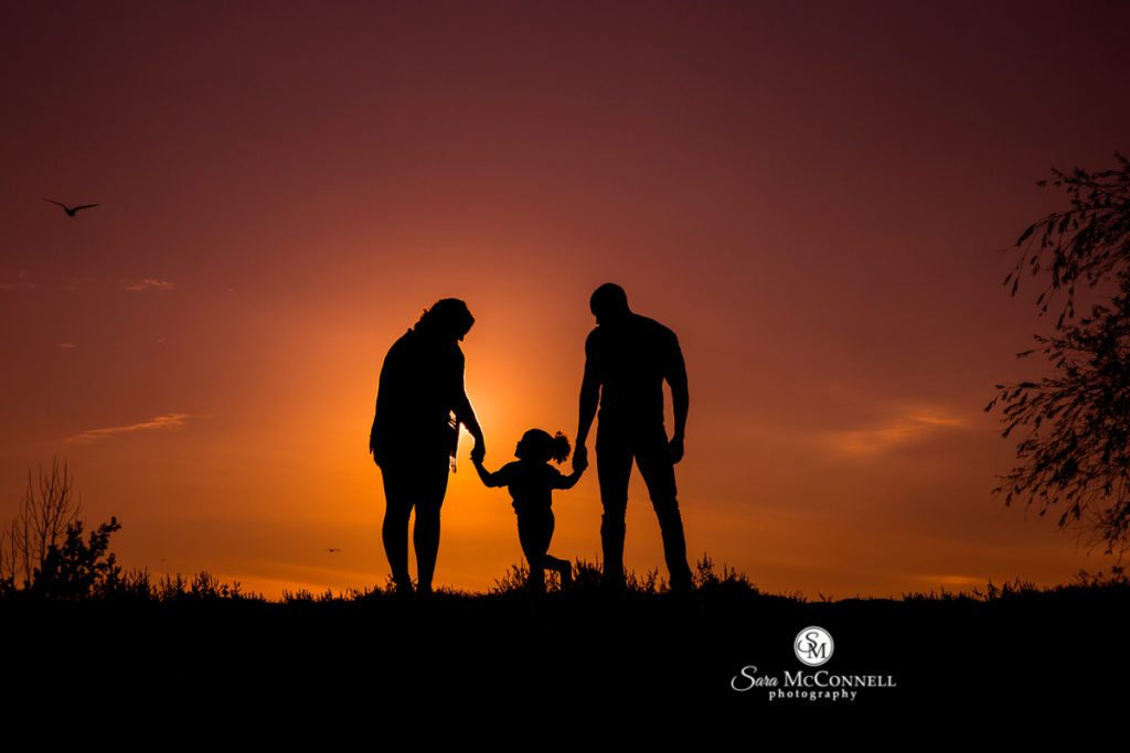 family holding hands as the sun sets