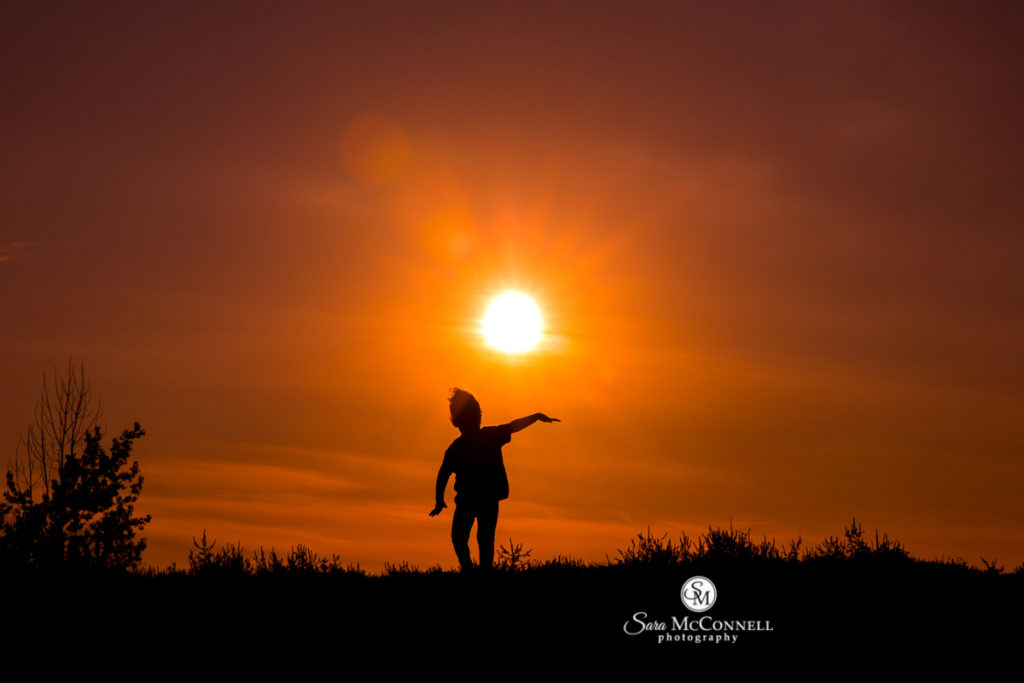 child dancing as the sun sets