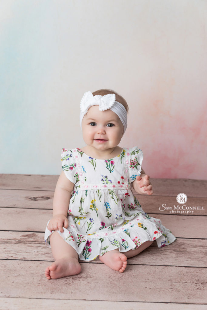 8 month old baby in a flower dress wearing a white headband