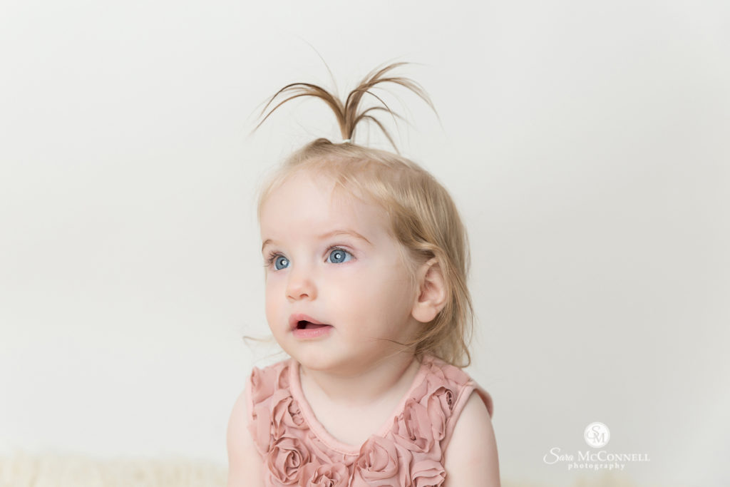 girl turning 1 wearing a pink dress and pigtail