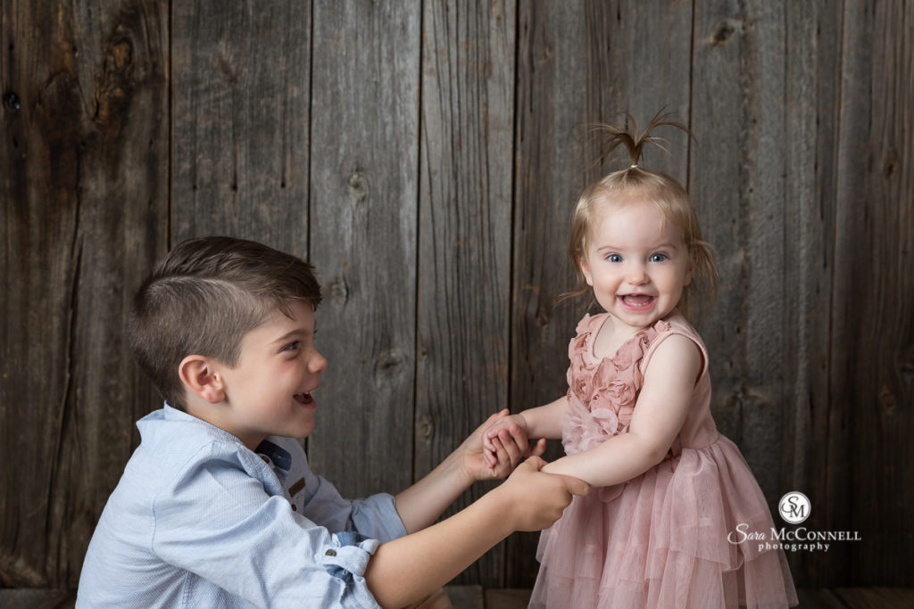 little girl in pink dress with her big brother