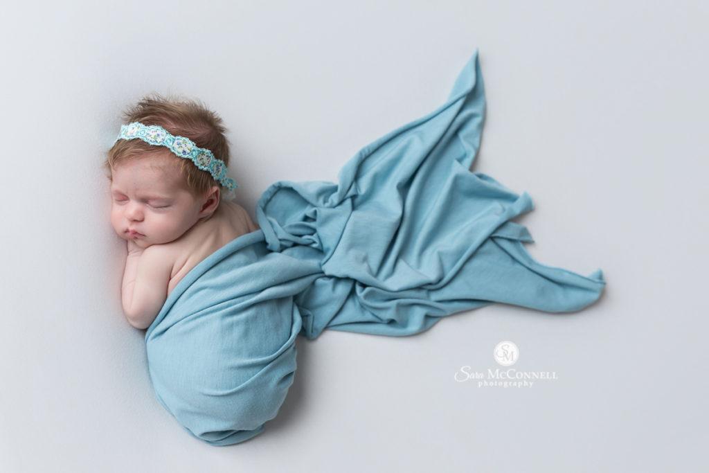 sleeping newborn wrapped in blue