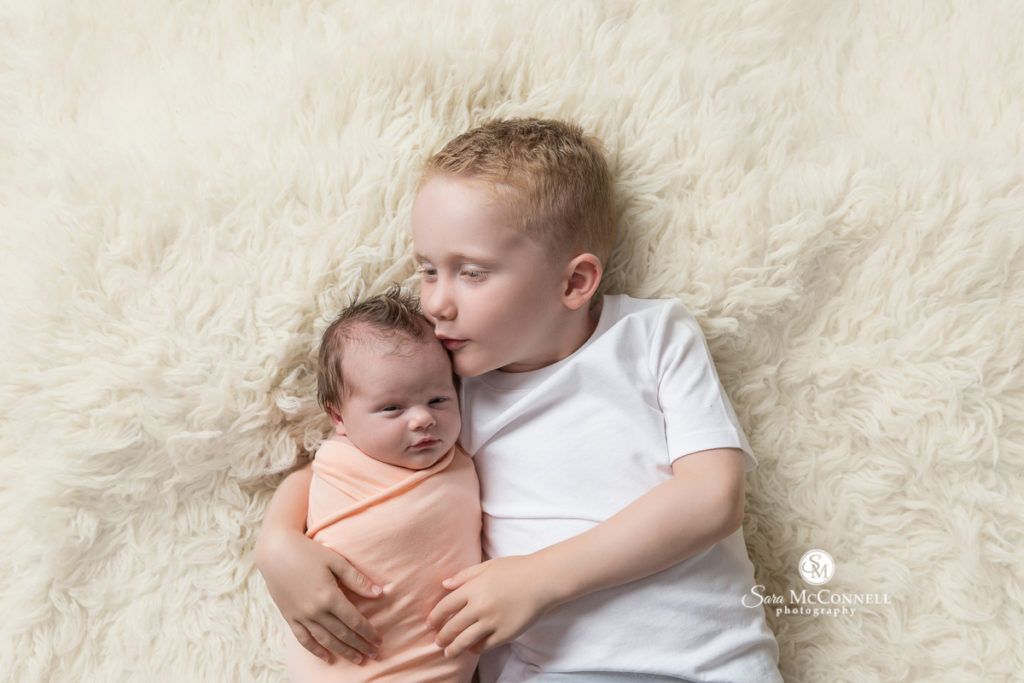 big brother snuggling new baby sister