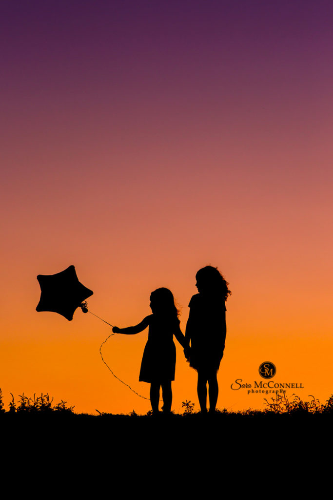 two sisters at sunset holding a balloon