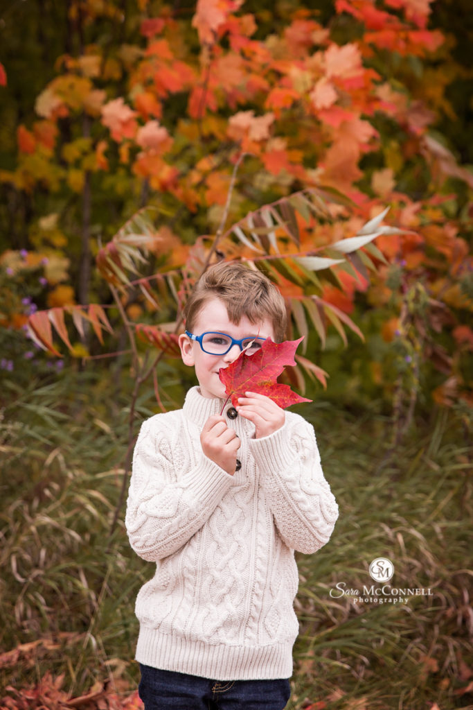young boy holding fall leaf
