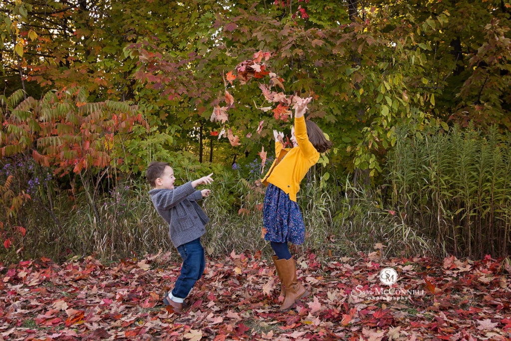 siblings throwing leaves