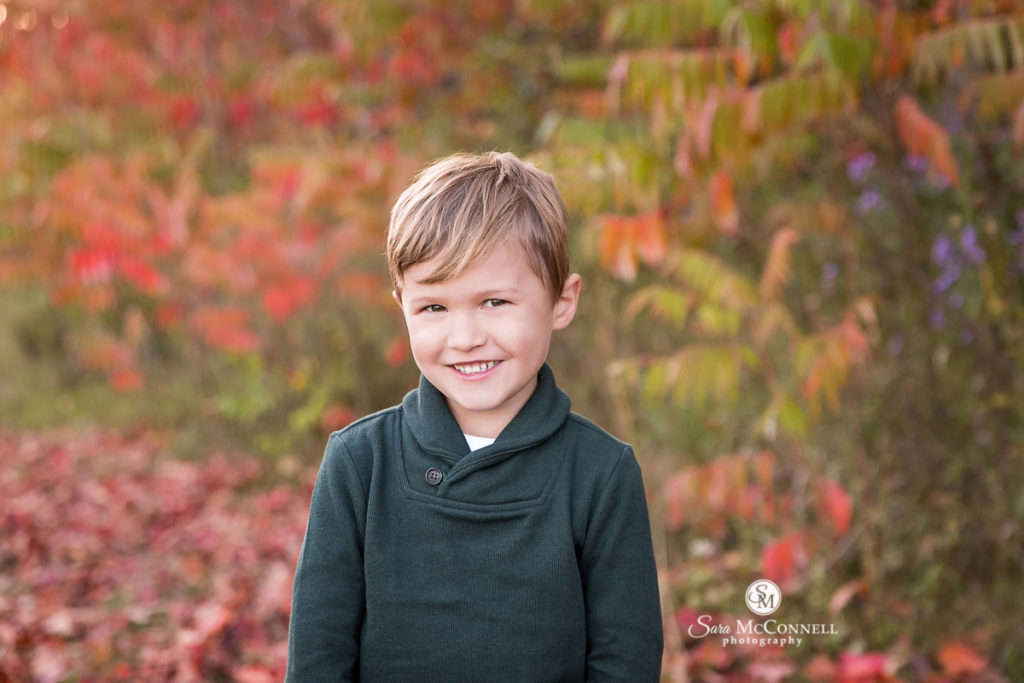young child smiling outside in the leaves