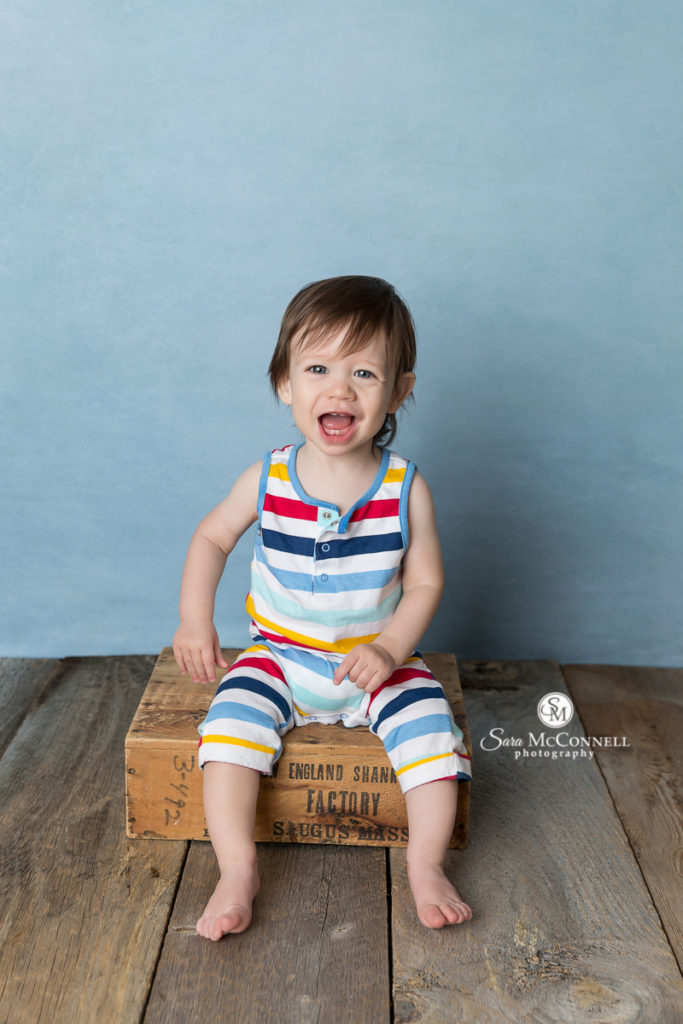 one year old in striped romper smiling