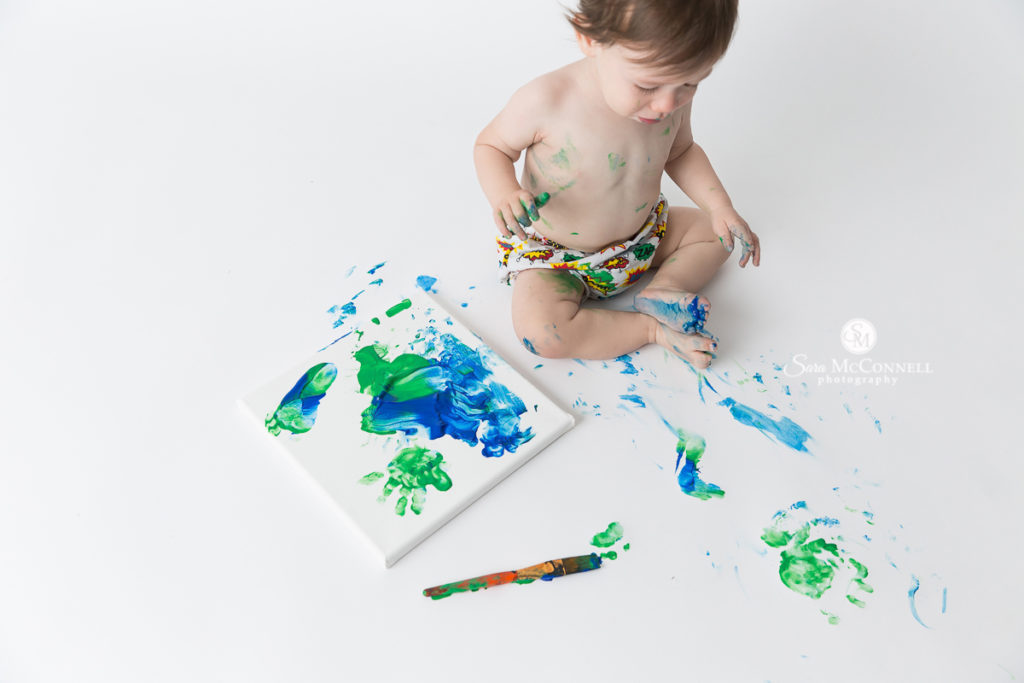 one year old painting with green and blue paint