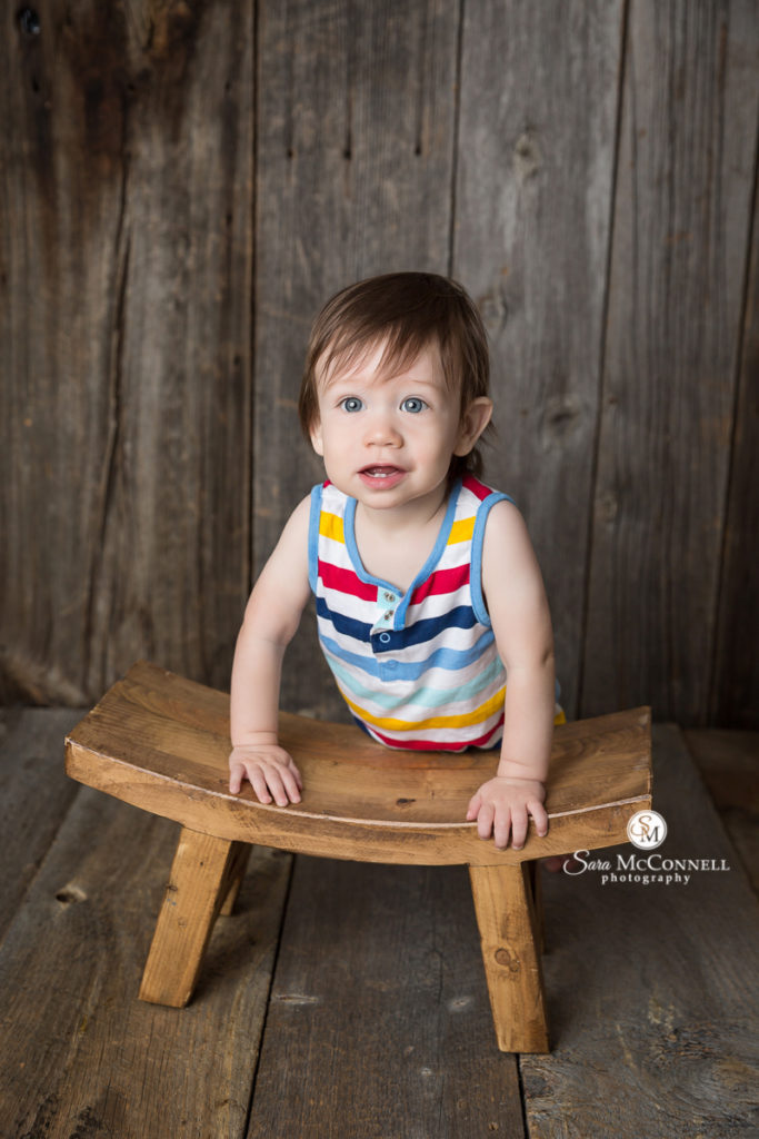one year old leaning against a wooden stool