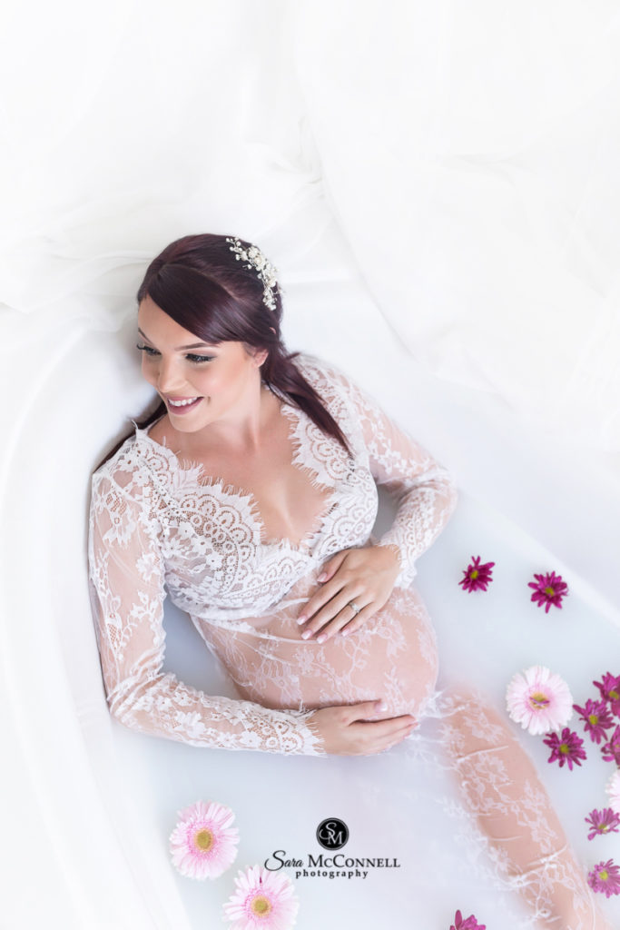 expectant woman in a lace gown in a milk bath with flowers