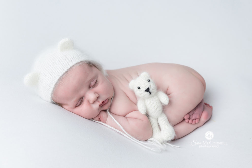 newborn baby wearing white knit hat