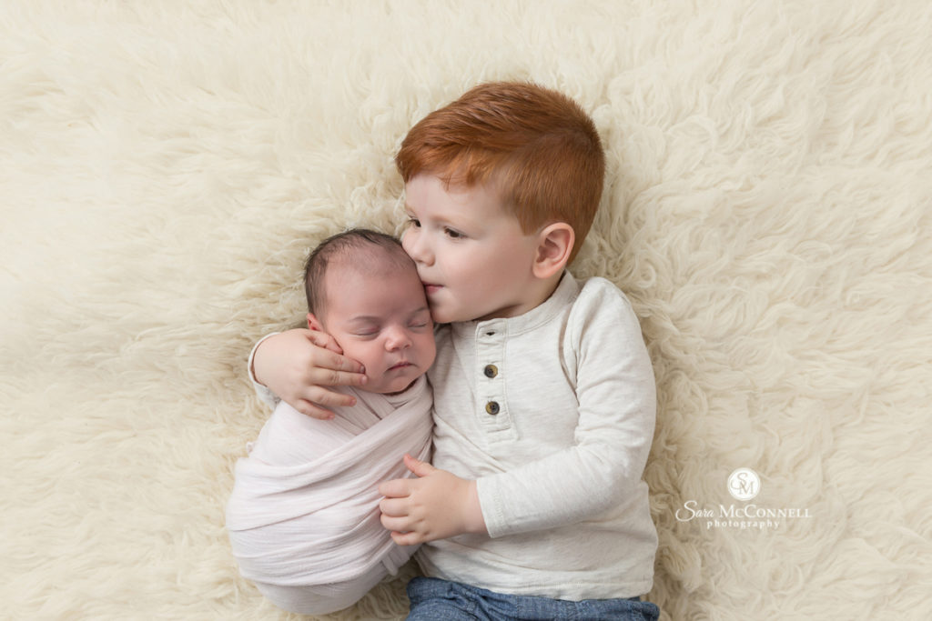 big brother kissing newborn baby