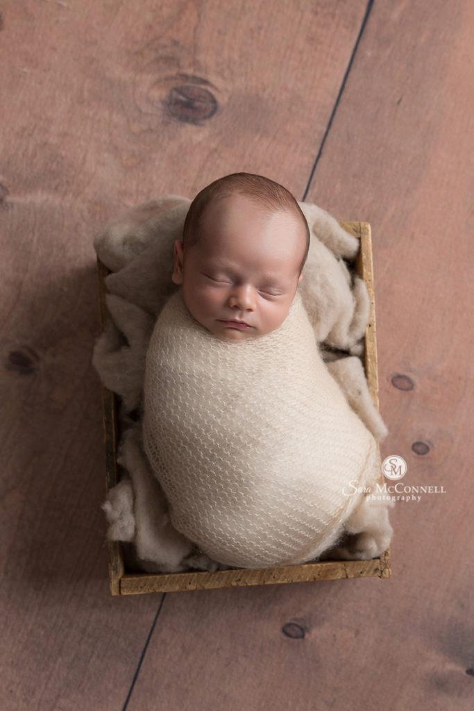 sleeping newborn baby in a wood basket