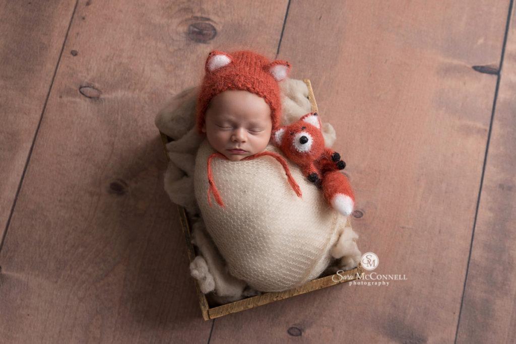 sleeping baby wearing a fox knit hat