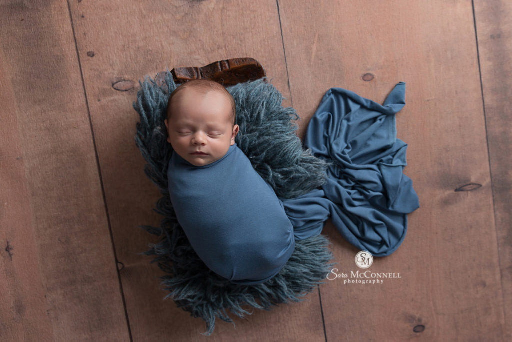 sleeping baby wrapped in blue blanket and sleeping on a blue fur rug in a wood basket