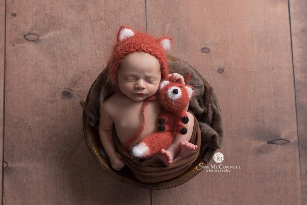 sleeping baby holding stuffed fox