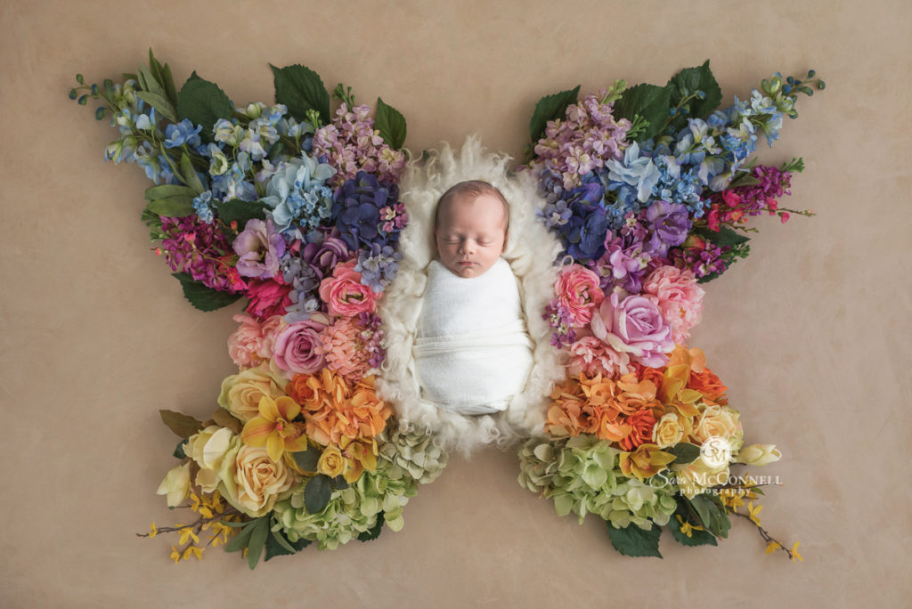 sleeping baby in a pile of flowers shaped like butterfly wings