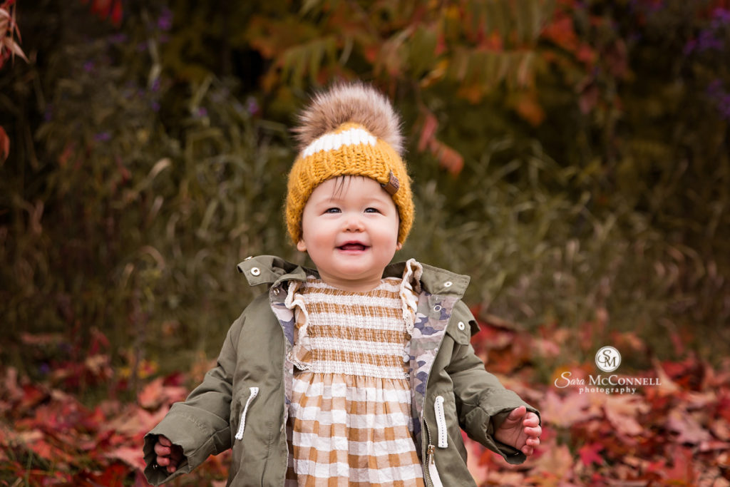 toddler in fall leaves