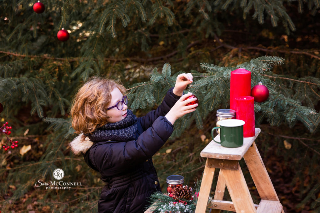 girl hanging holiday ornament on tree