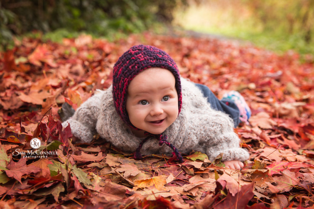 baby lying in fall leaves