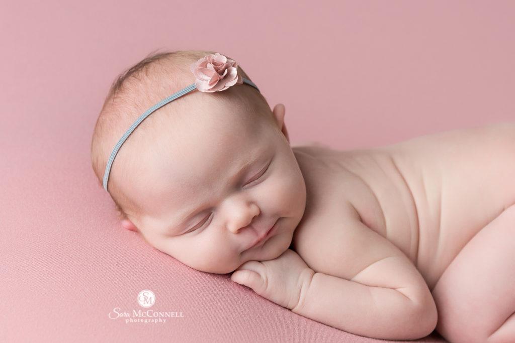 sleeping newborn baby on a pink blanket wearing a headband