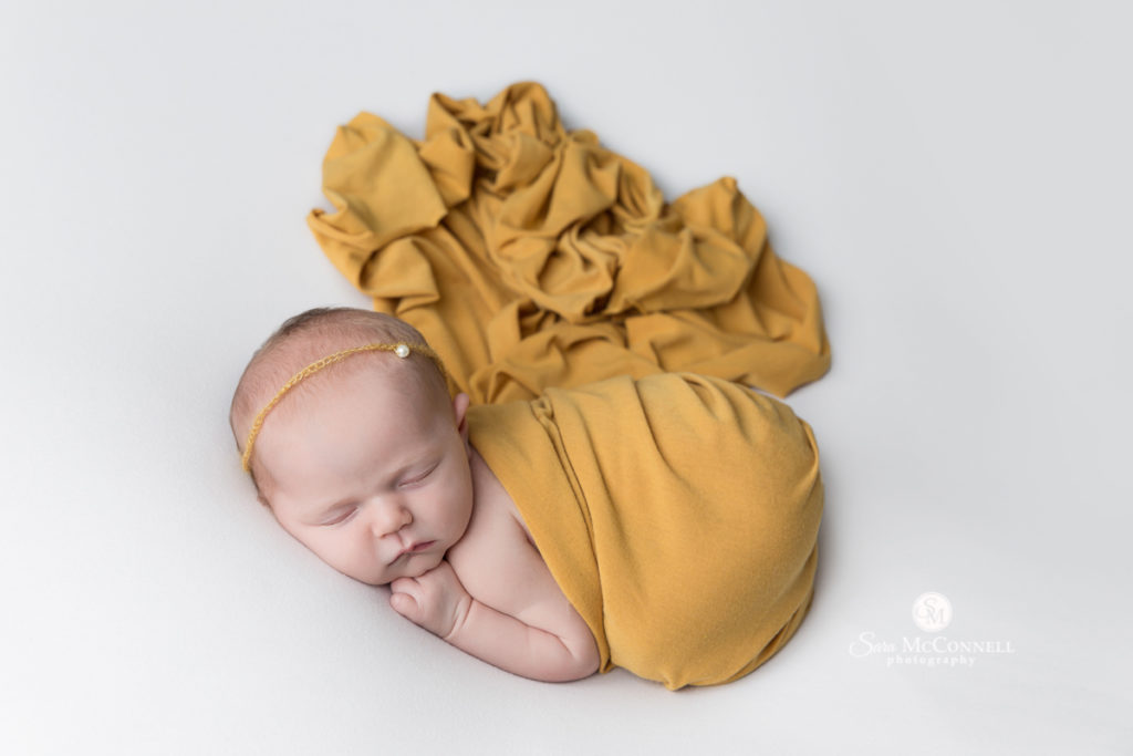 newborn baby wrapped in yellow