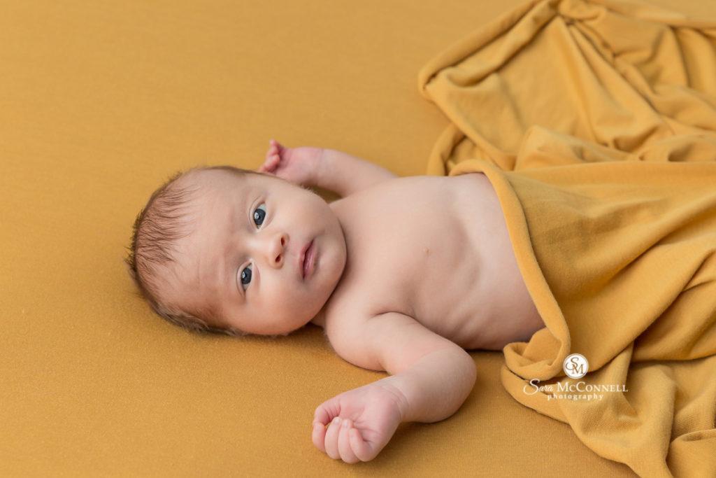 newborn baby awake and wrapped in yellow