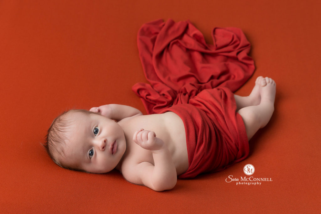newborn baby awake and wrapped in red